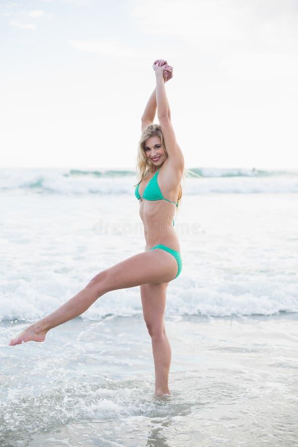 Donna bionda allegra in bikini verde che gioca nelle onde fotografia stock