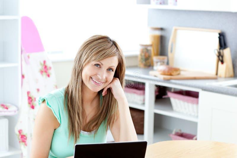 Donna bionda allegra che usando il suoi computer portatile e sorridere fotografie stock libere da diritti