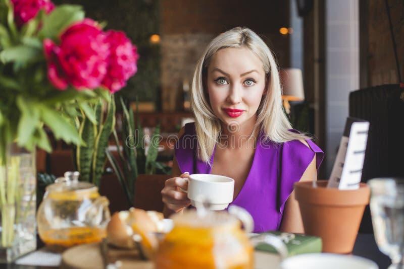 Donna bionda allegra in ristorante, ritratto immagini stock