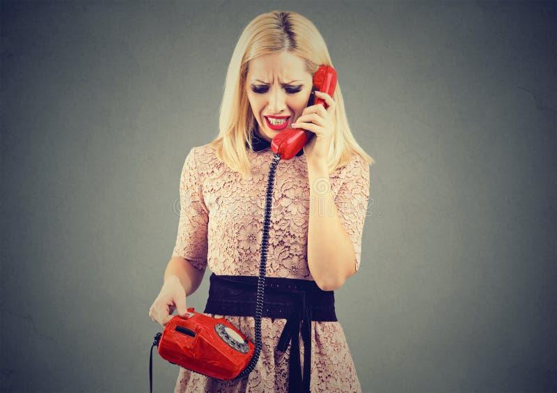Donna bionda arrabbiata che riceve cattive notizie sul telefono fotografie stock