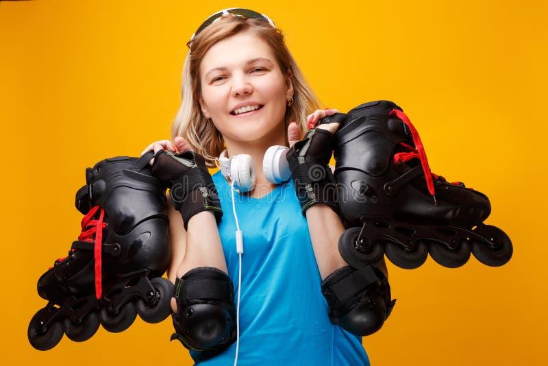 Donna bionda atletica felice con i pattini di rullo sulla spalla in studio fotografia stock libera da diritti