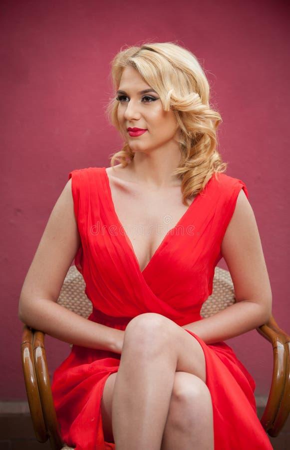 Donna bionda attraente alla moda in vestito rosso che si siede sulla sedia Bella donna elegante con il fiore rosso nella posa dei fotografia stock libera da diritti