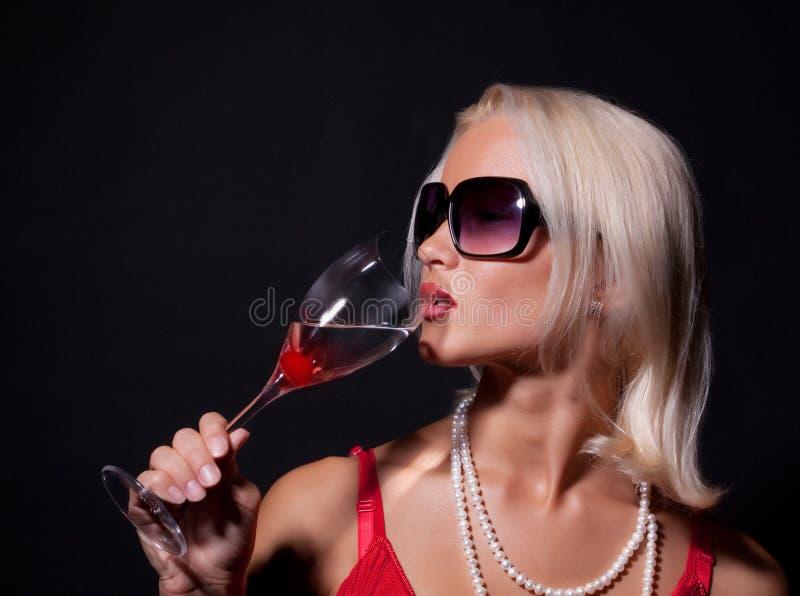 Donna bionda attraente che beve il suo cocktail immagini stock