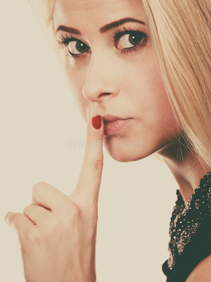 Donna bionda attraente che fa gesto di silenzio fotografia stock libera da diritti