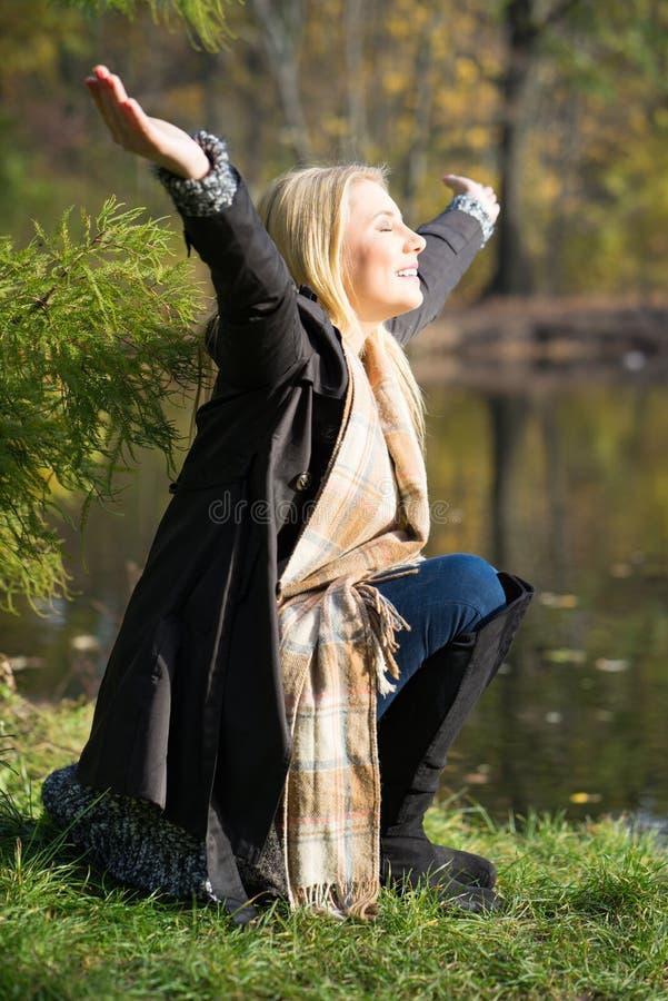 Donna bionda attraente che gode del sole di autunno immagini stock