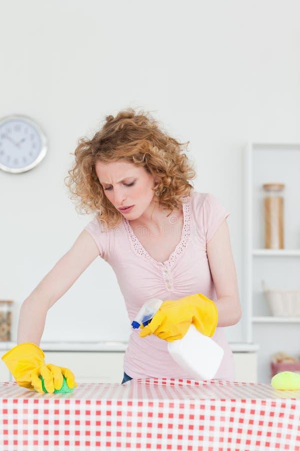 Donna bionda attraente che pulisce una scheda di taglio fotografia stock
