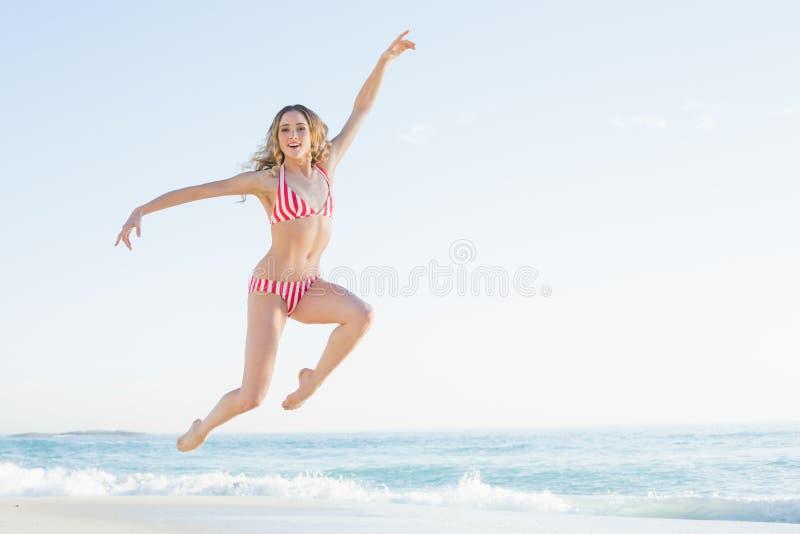 Donna bionda attraente che salta sulla spiaggia fotografia stock