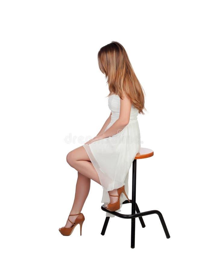 Donna bionda attraente che si siede su un panchetto fotografia stock libera da diritti
