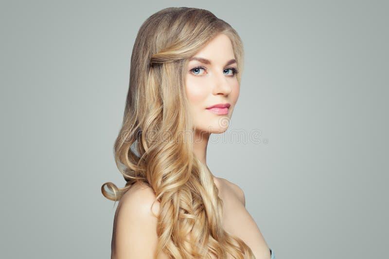 Donna bionda attraente con pelle sana e capelli ricci Concetto facciale di trattamento, del haircare e di cosmetologia immagini stock libere da diritti