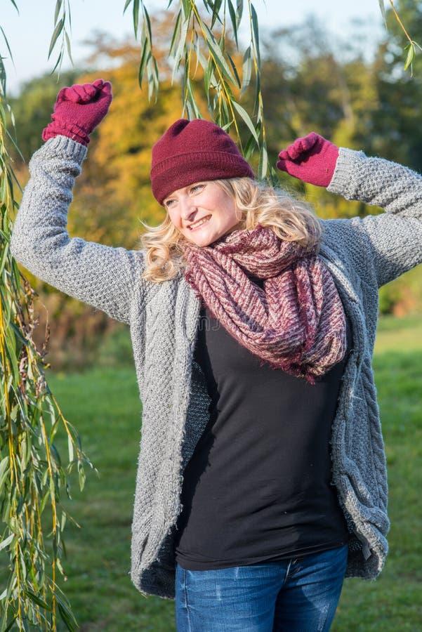 Donna bionda attraente in un parco autunnale immagini stock