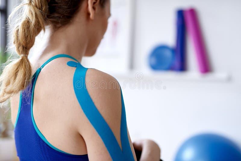 Donna bionda attraente in un ufficio luminoso di terapia di sport con nastro adesivo di kinesio sul suoi collo e spalla per guari fotografia stock