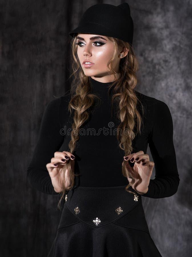 Donna bionda attraente in vestito nero fotografia stock libera da diritti
