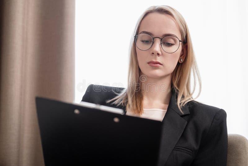 Donna bionda attraente in vetri e un funzionamento del vestito su una compressa, parlante sul telefono e prendente le note in a immagini stock libere da diritti