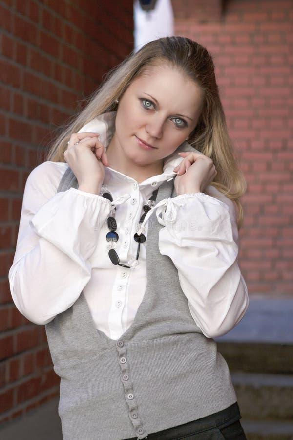 Donna bionda caucasica in camicia bianca che posa contro il muro di mattoni fotografia stock