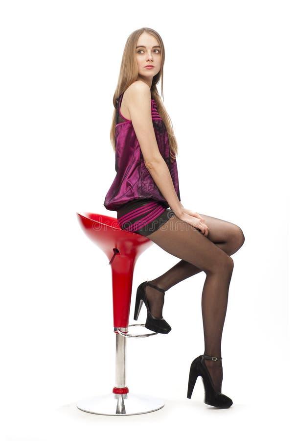 Donna bionda caucasica elegante in vestito sulla barra immagine stock