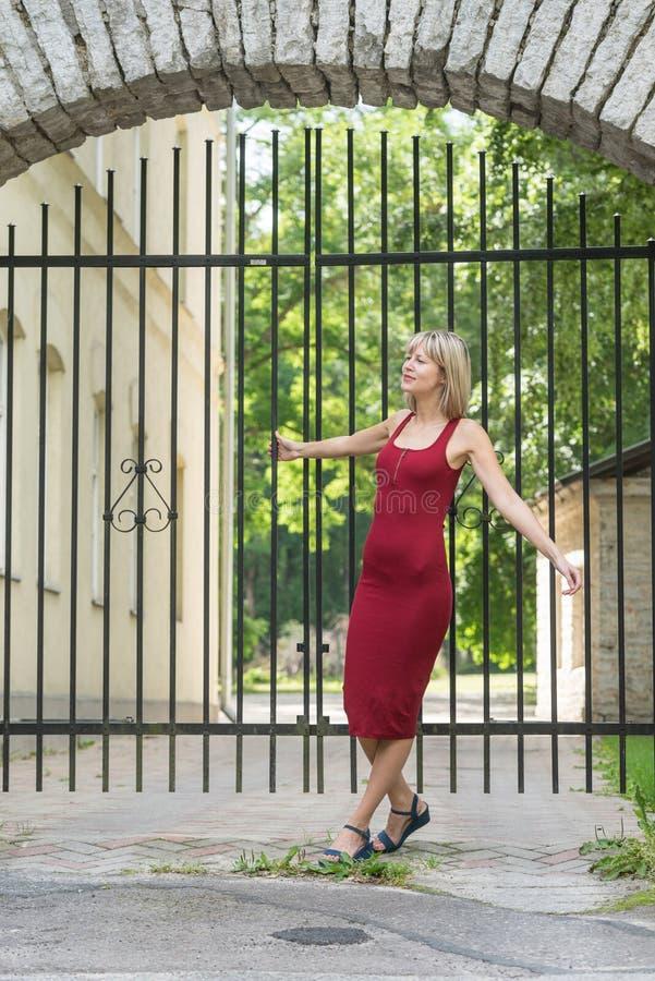 Donna bionda che abbraccia un albero in parco Ragazza in un vestito rosso che riposa in natura, pesa contro un albero fotografia stock