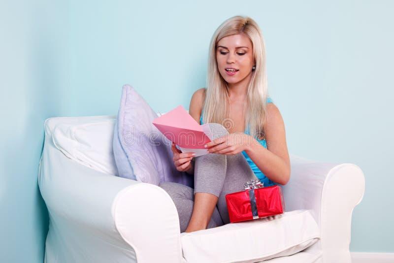 Donna bionda che apre una scheda di compleanno immagini stock libere da diritti