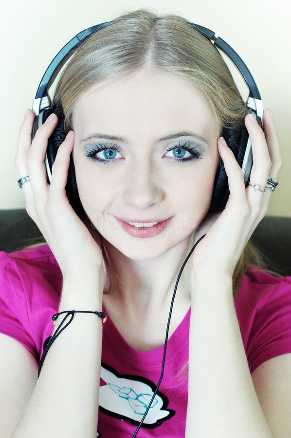 Donna bionda che ascolta sorridere di musica fotografie stock