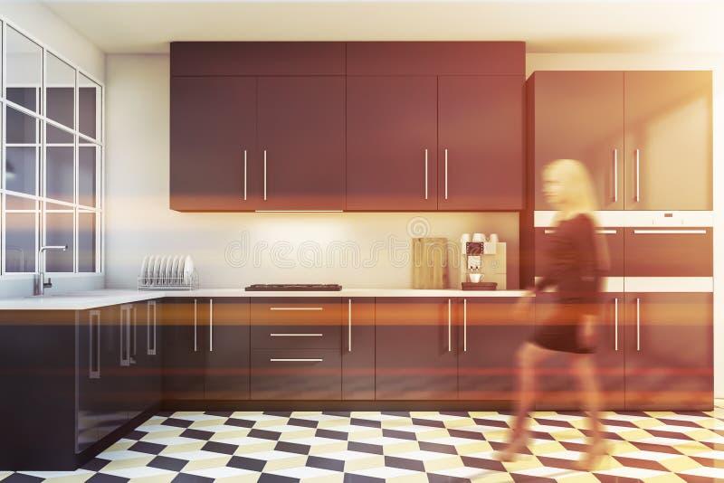 Donna bionda che cammina nella cucina bianca e grigia immagini stock
