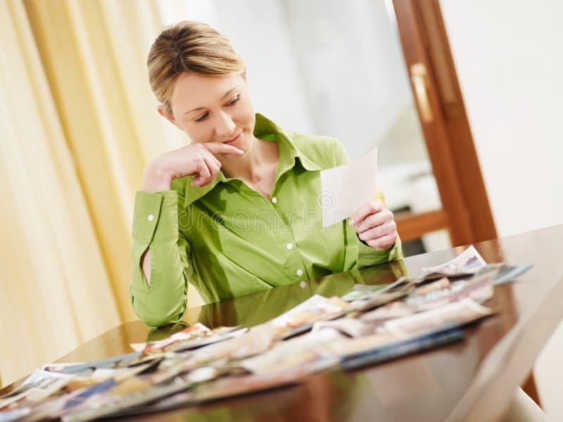 Donna bionda che esamina le foto immagine stock