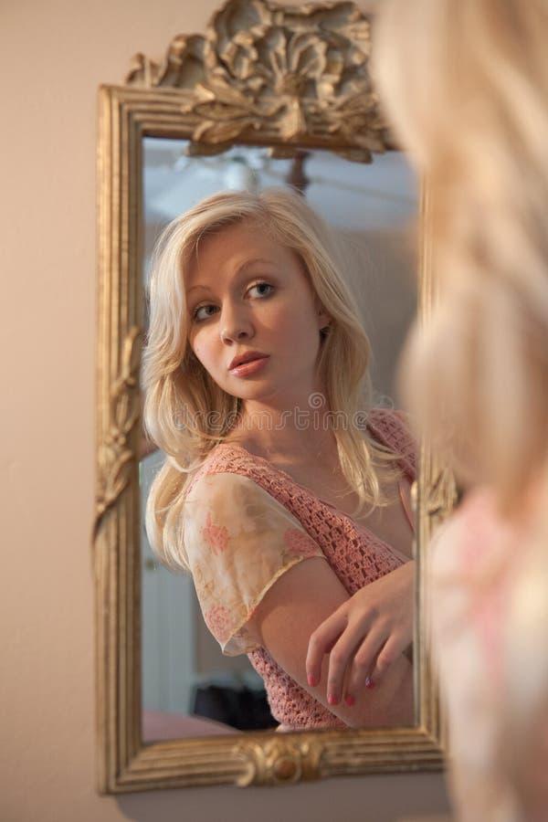 Donna bionda che guarda all'auto in specchio immagini stock libere da diritti