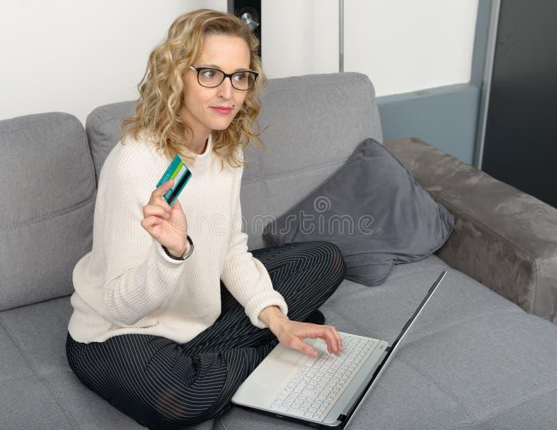 Donna bionda che per mezzo del computer portatile per comperare fotografia stock