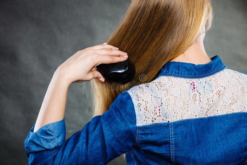Donna bionda che pettina i suoi capelli immagine stock libera da diritti