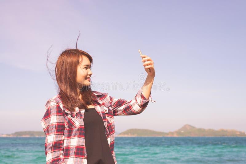 Donna bionda che prende selfie facendo uso dello smartphone allo stile di vita di viaggio per mare ed al concetto moderno di tecn immagine stock