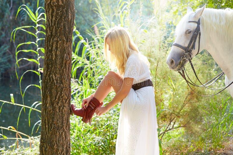 Donna bionda che ripara il suo stivale con il cavallo bianco fotografia stock