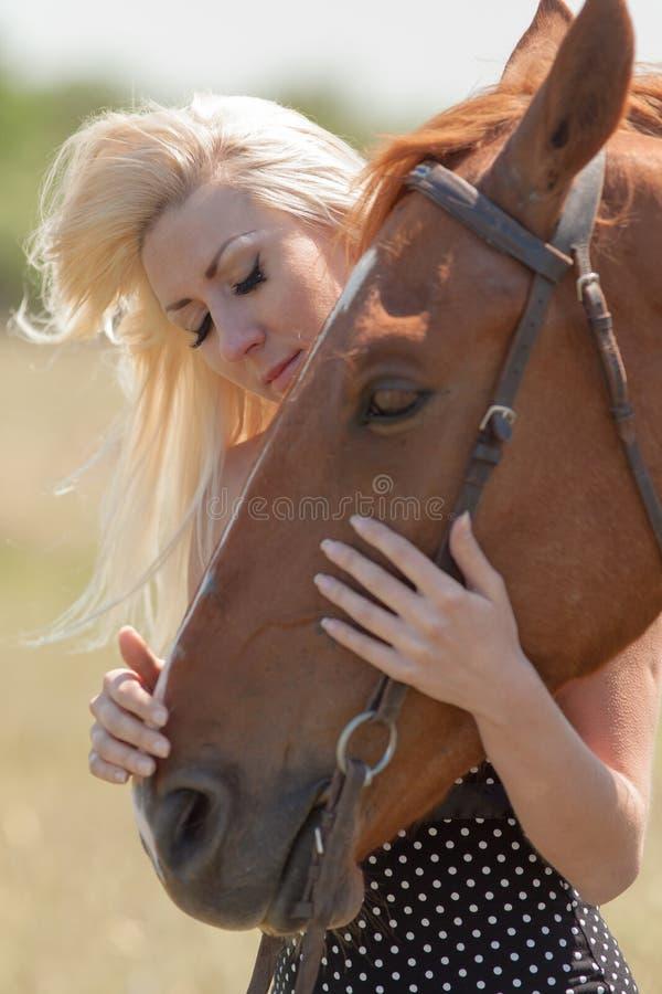 Donna bionda che segna cavallo castrato immagini stock