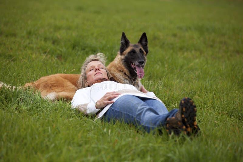 Donna bionda che si distende con il suo cane fotografie stock libere da diritti