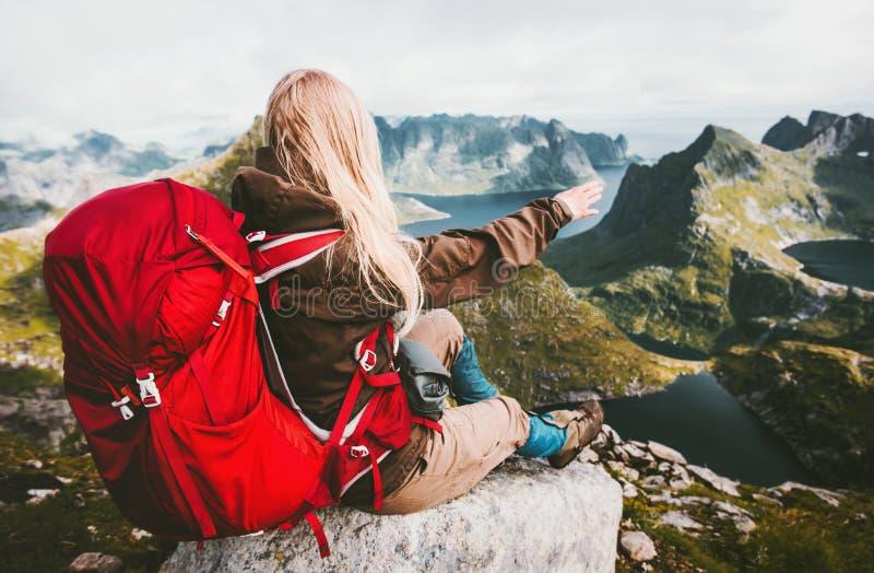 Donna bionda che si rilassa da solo con lo zaino rosso in montagne fotografia stock