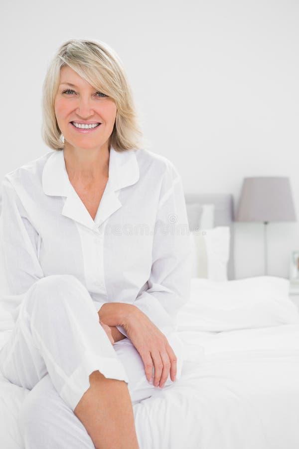 Donna bionda che si siede fornito di gambe trasversale nella sua camera da letto fotografia stock libera da diritti