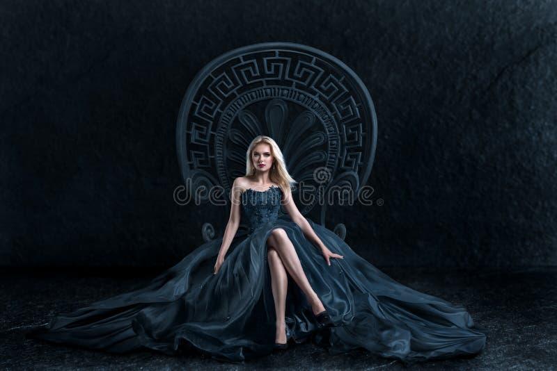 Donna bionda che si siede sul trono fotografia stock libera da diritti