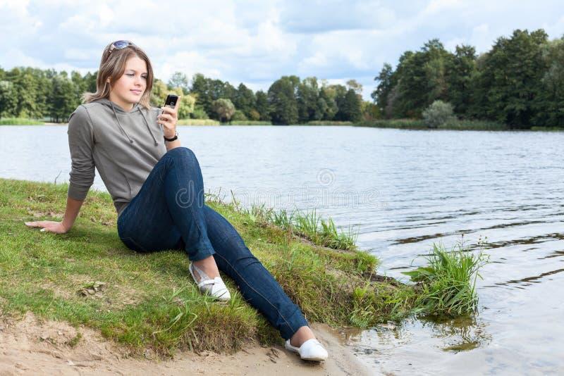 Donna bionda che si siede sulla sponda del fiume con il telefono cellulare a disposizione, esaminando schermo fotografia stock libera da diritti