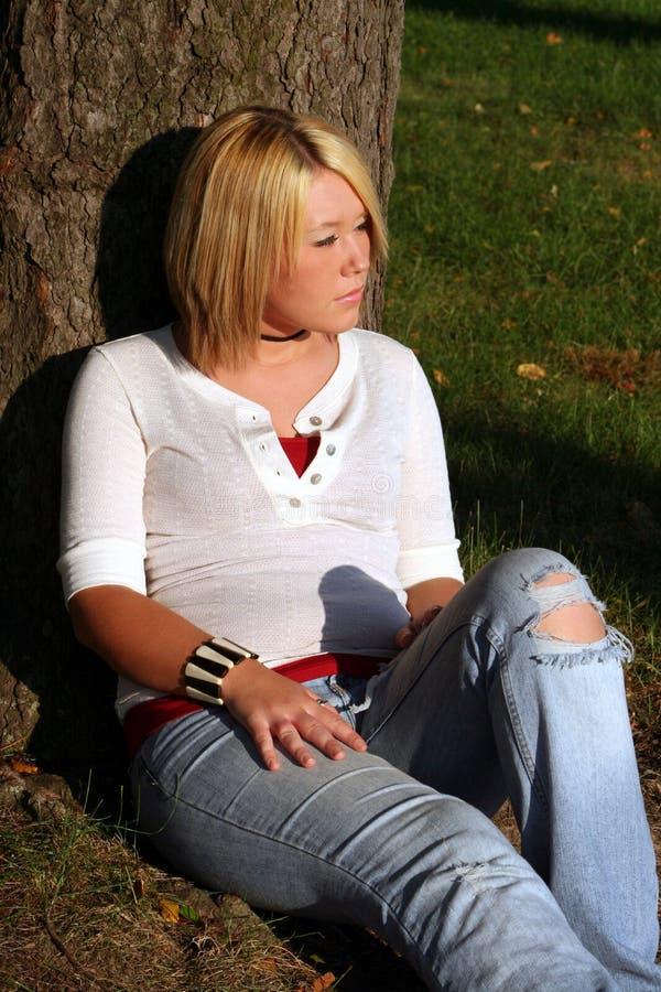 Donna bionda che si siede sulla terra fotografia stock libera da diritti