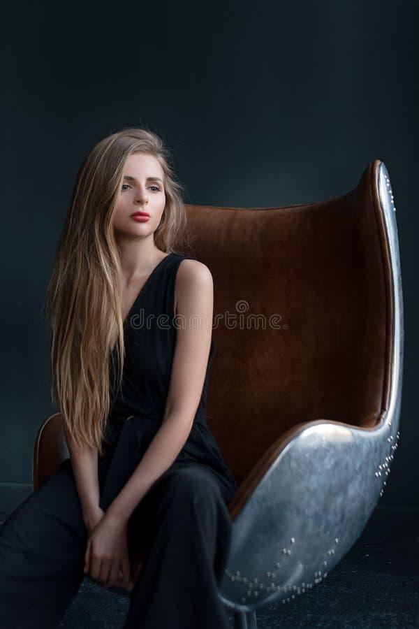 Donna bionda che si siede in una sedia nello stile di stile Liberty Affare, donna di affari elegante Ritratto scuro interno fotografia stock