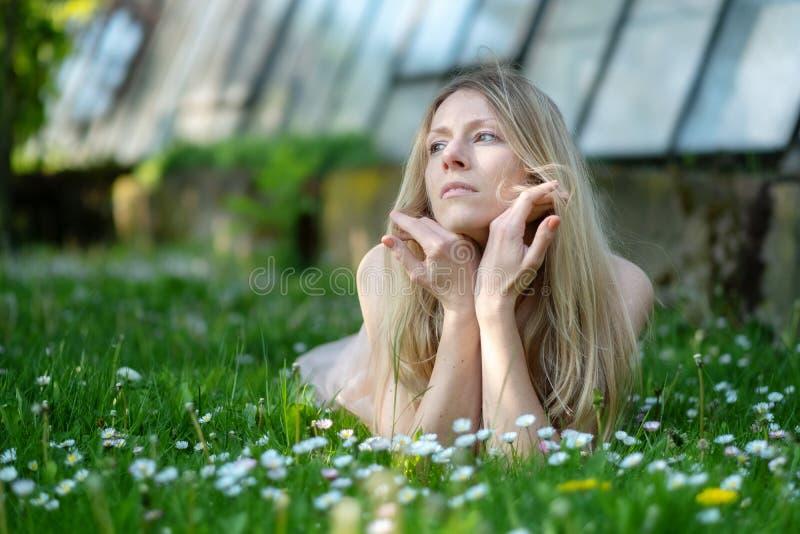 Donna bionda che si trova meditatamente in un giardino del campo con le margherite fotografia stock