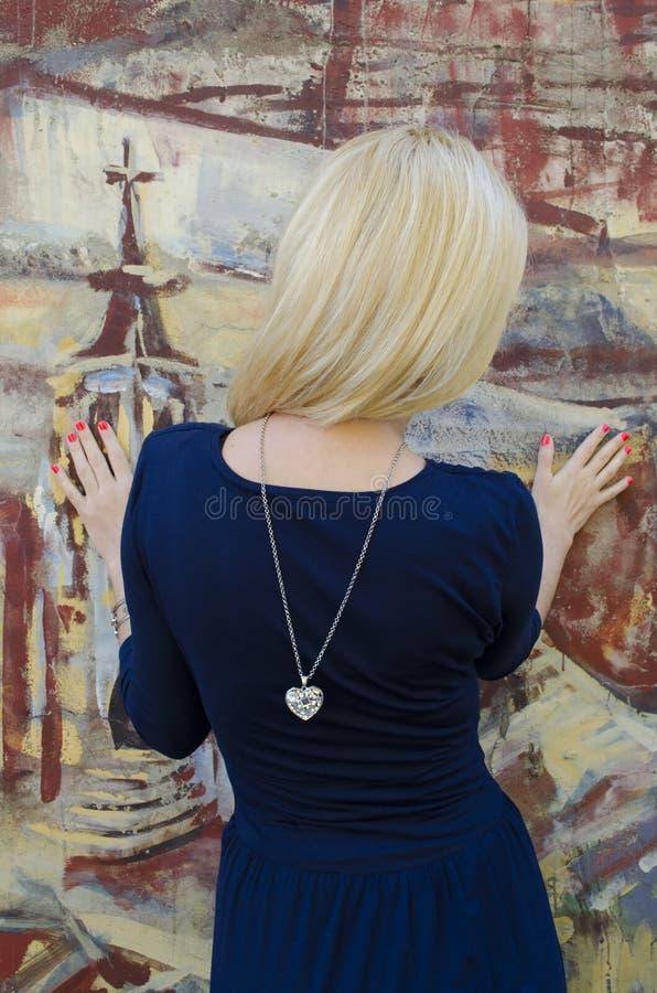 Donna bionda che sta vicino all'immagine con la grafite dipinta fotografia stock