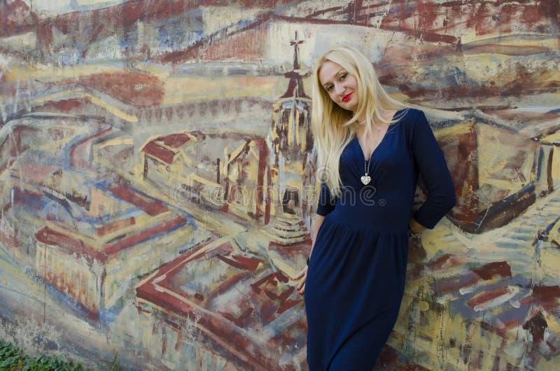 Donna bionda che sta vicino all'immagine con la grafite dipinta fotografia stock libera da diritti