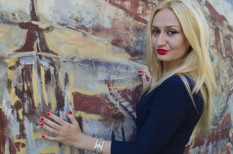 Donna bionda che sta vicino all'immagine con la grafite dipinta fotografie stock libere da diritti
