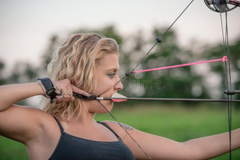 Donna bionda che tende un arco di caccia in un'area boscosa fotografia stock libera da diritti