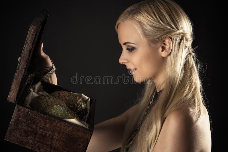 Donna bionda che tiene una scatola con i draghi delle uova immagini stock libere da diritti