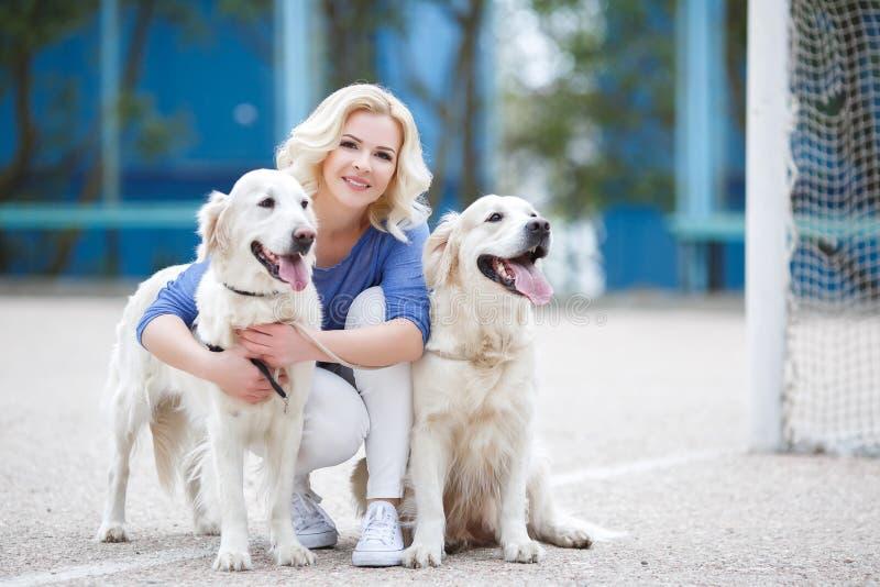 Donna bionda con due labrador retriever dorati all'aperto fotografia stock