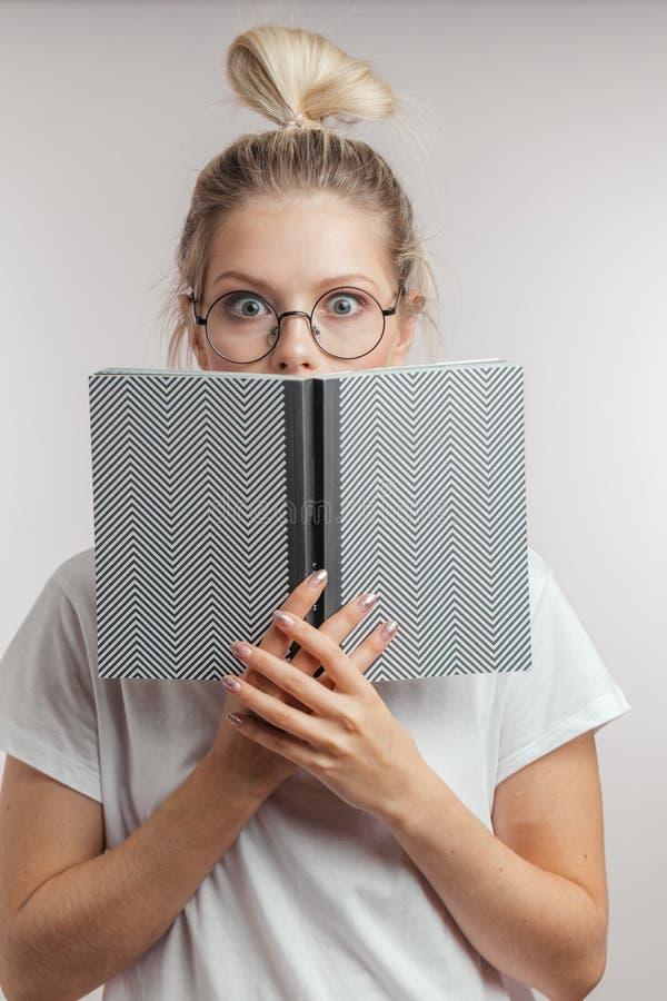 Donna bionda con gli occhi colpiti che si nascondono dietro un libro aperto e che esaminano macchina fotografica immagine stock libera da diritti
