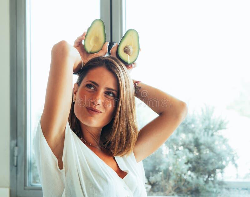 Donna bionda con gli occhi verdi nella parte moderna della cucina un avocado da giocare con metterlo sugli occhi e sulla testa immagini stock