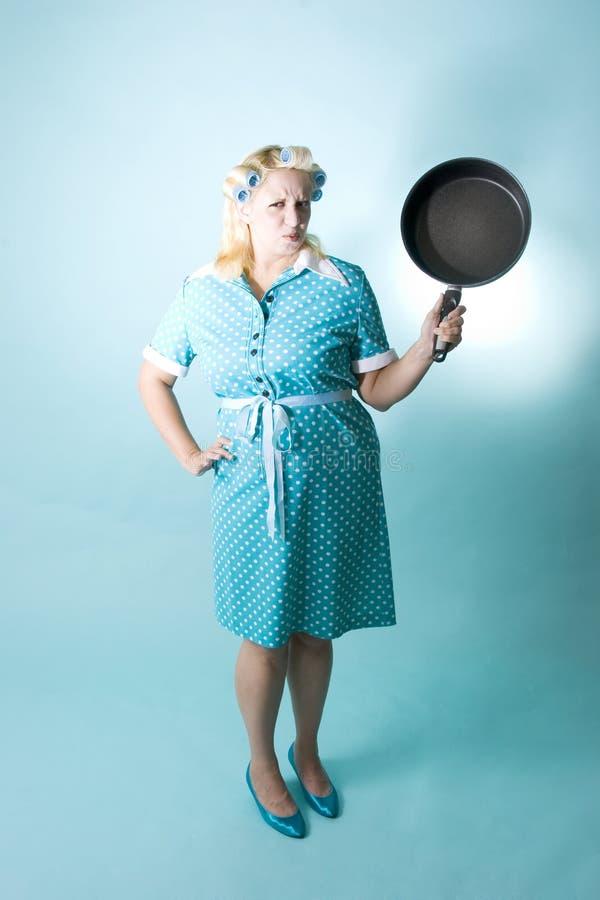 Donna bionda con i bigodini in suoi capelli e vaschetta di frittura fotografie stock libere da diritti