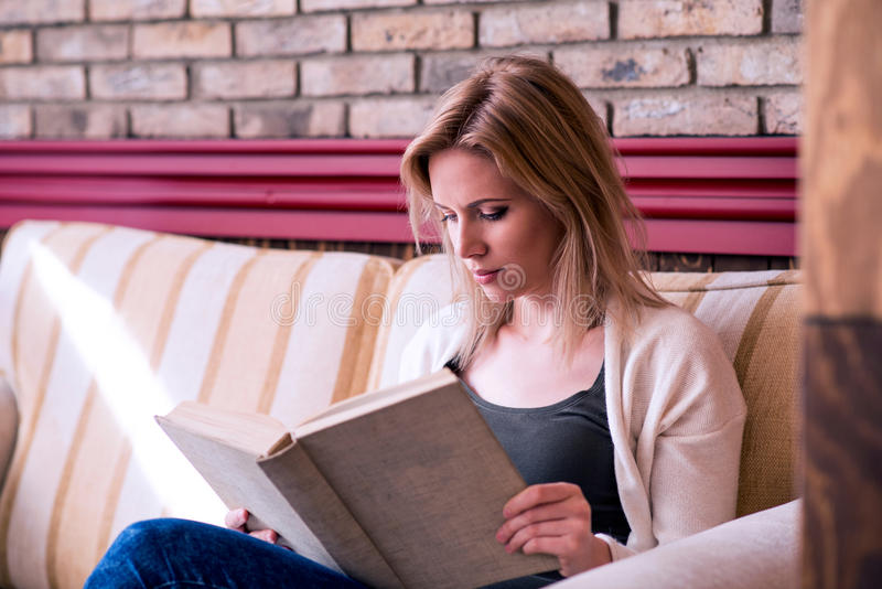 Donna bionda con il giornale in caffè bevente del caffè immagine stock