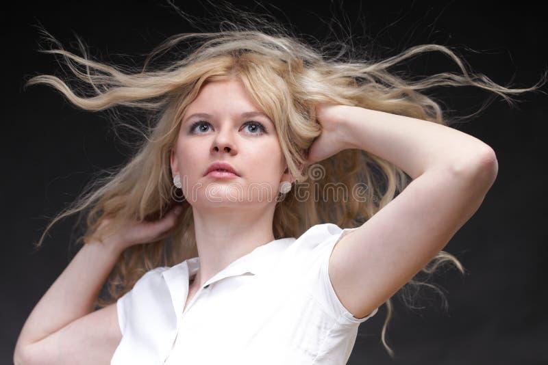 Donna bionda con il suo salto dei capelli fotografia stock libera da diritti