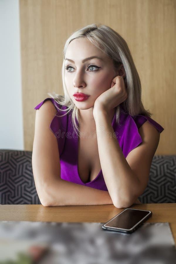 Donna bionda con il telefono cellulare in caffè fotografia stock